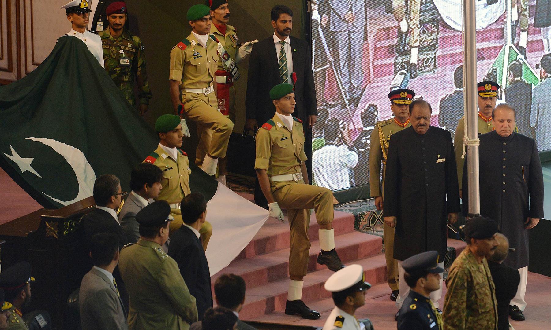 پاکستانی صدر ممنون حسین اور وزیراعظم نواز شریف کی جانب سے پرچم کشائی کی تقریب کے موقع پر پاکستانی فوجی قومی پرچم لے جارہے ہیں—اے ایف پی فوٹو۔
