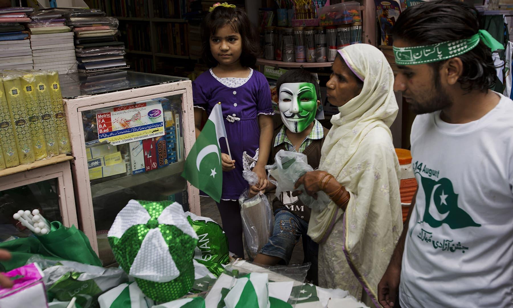 لوگ بڑی تعداد میں یوم آزادی کو منانے کے لیے اسٹالز سے بیچز اور پرچم خرید رہے ہیں — فوٹو اے پی
