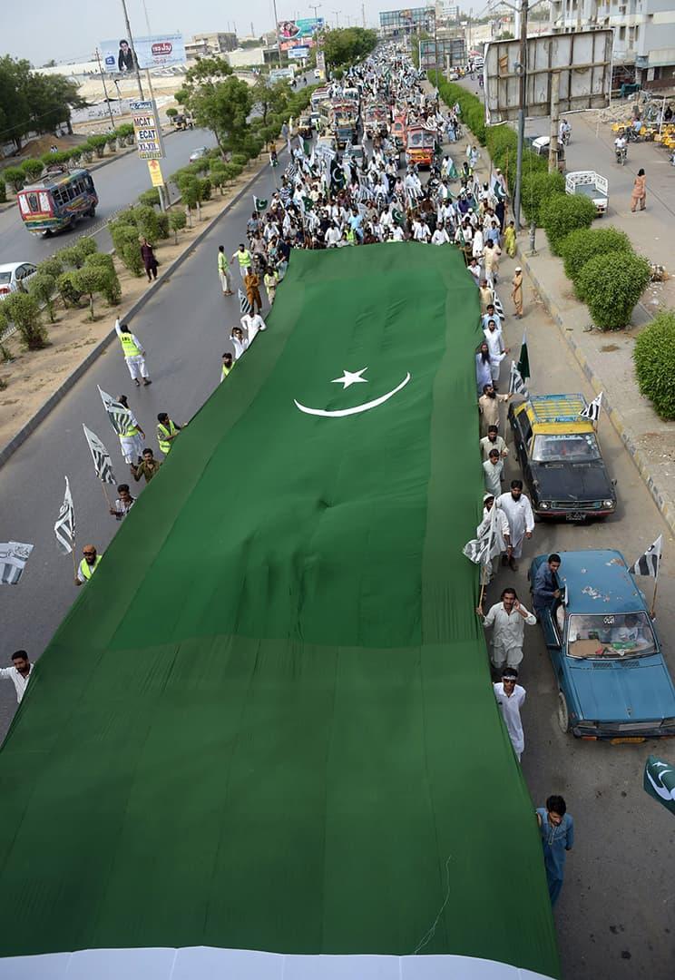 کراچی کی سڑکوں پر یوم آزادی کے حوالے سے بڑا پرچم نکالا گیا — فوٹو اے ایف پی