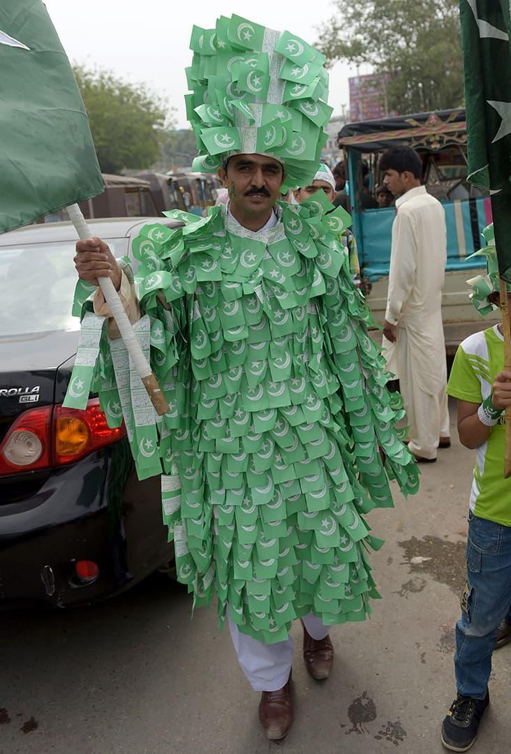 کراچی کا ایک آدمی قومی پرچم سے بنا لباس پہن کر یوم آزادی کا دن منا رہا ہے — فوٹو اے ایف پی