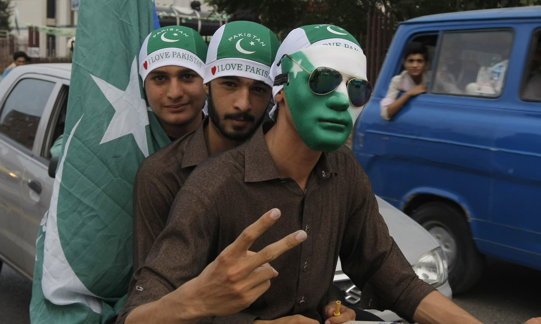 راولپنڈی میں ایک شخص نے پاکستانی جھنڈے کے رنگوں پر مشتمل ماسک پہن رکھا ہے — فوٹو اے پی