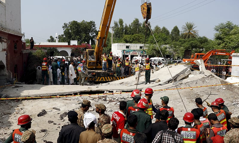 Rescue workers use a crane to lift sections of the collapsed roof after a blast near the home of the home minister of Punjab, Shuja Khanzada. —Reuters