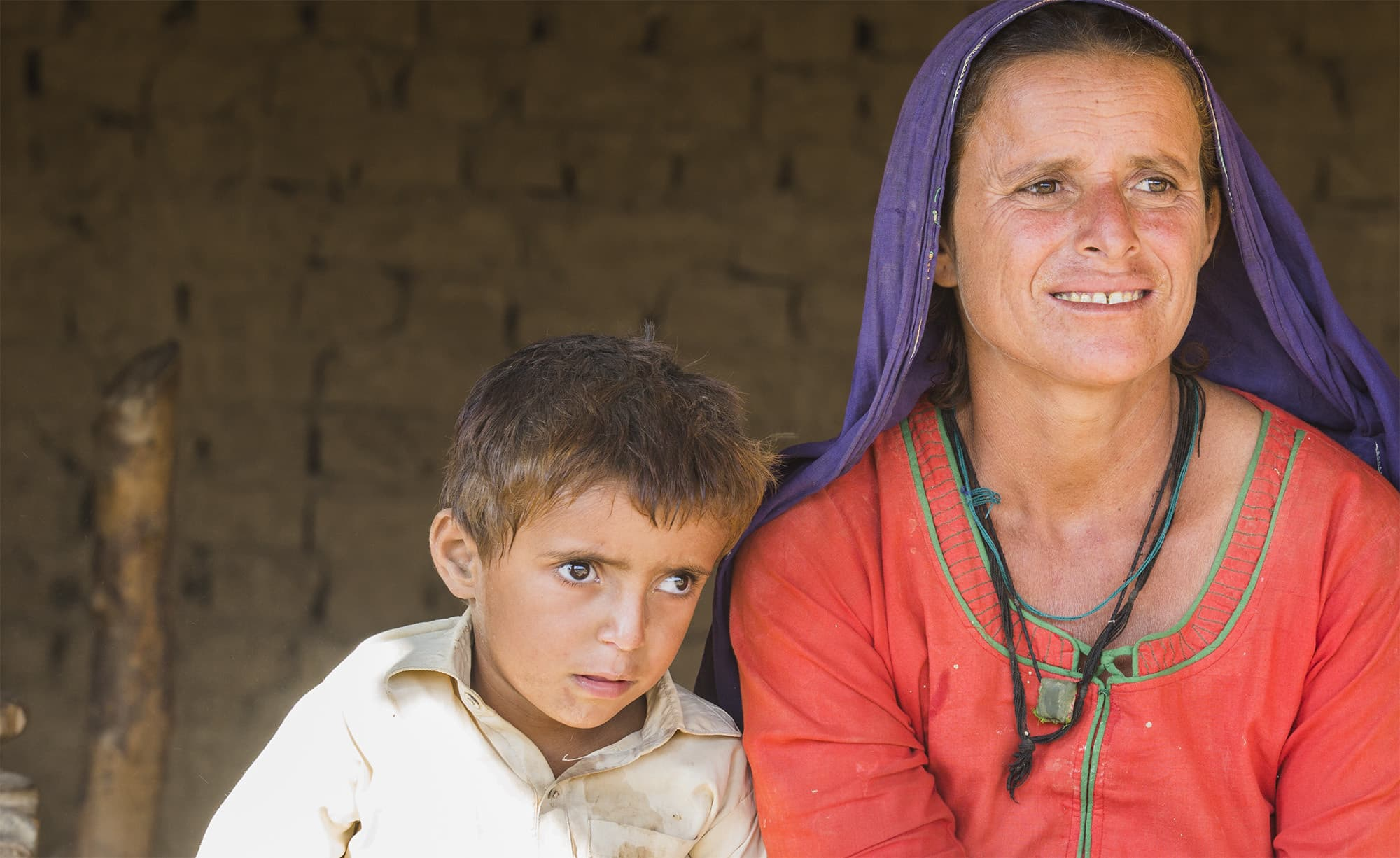Zahida, a local of Allah Bux Tewna, a village in Dadu is pictured in her home with her son. - Photo by Shameen Khan
