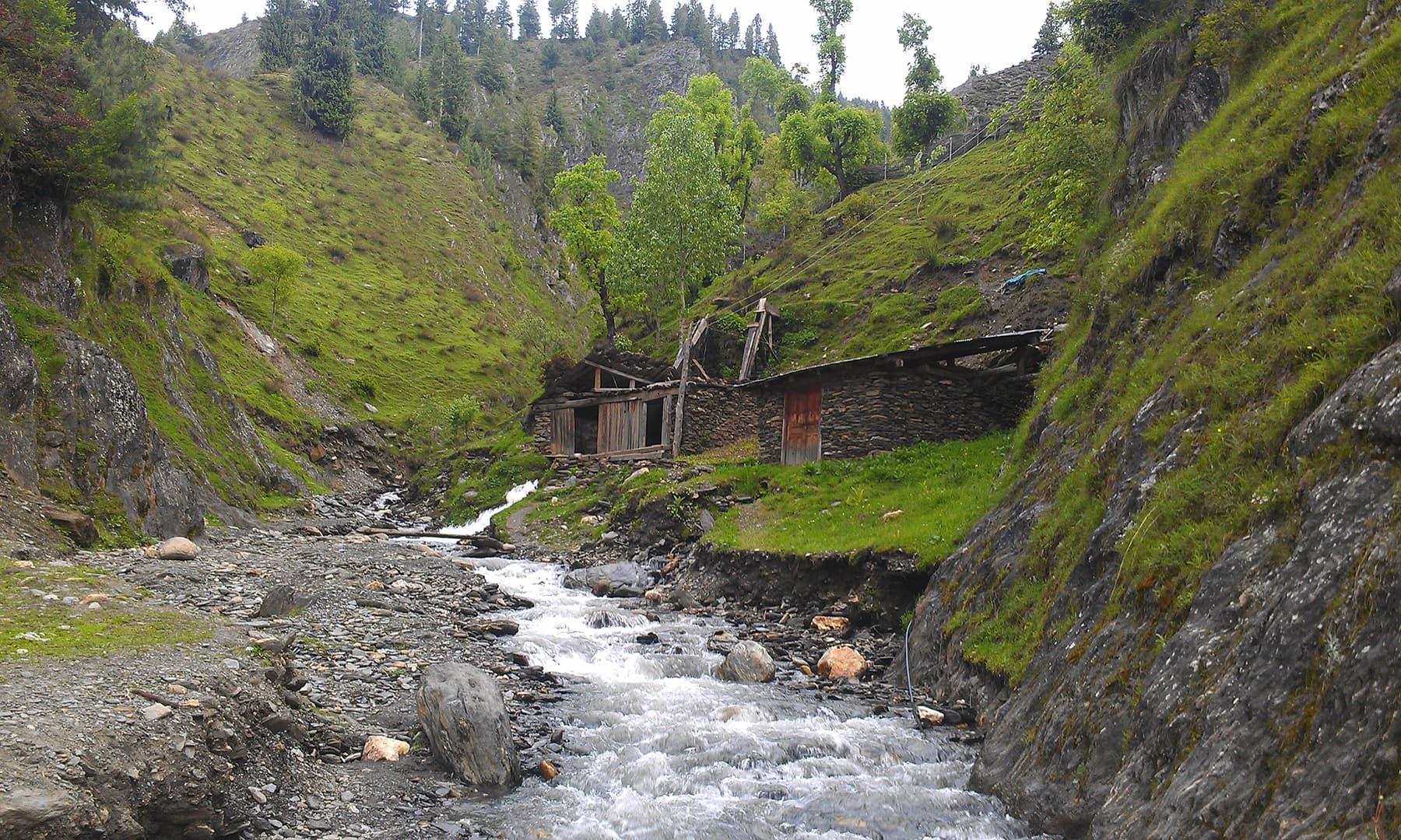 A shack next to a glacial stream.