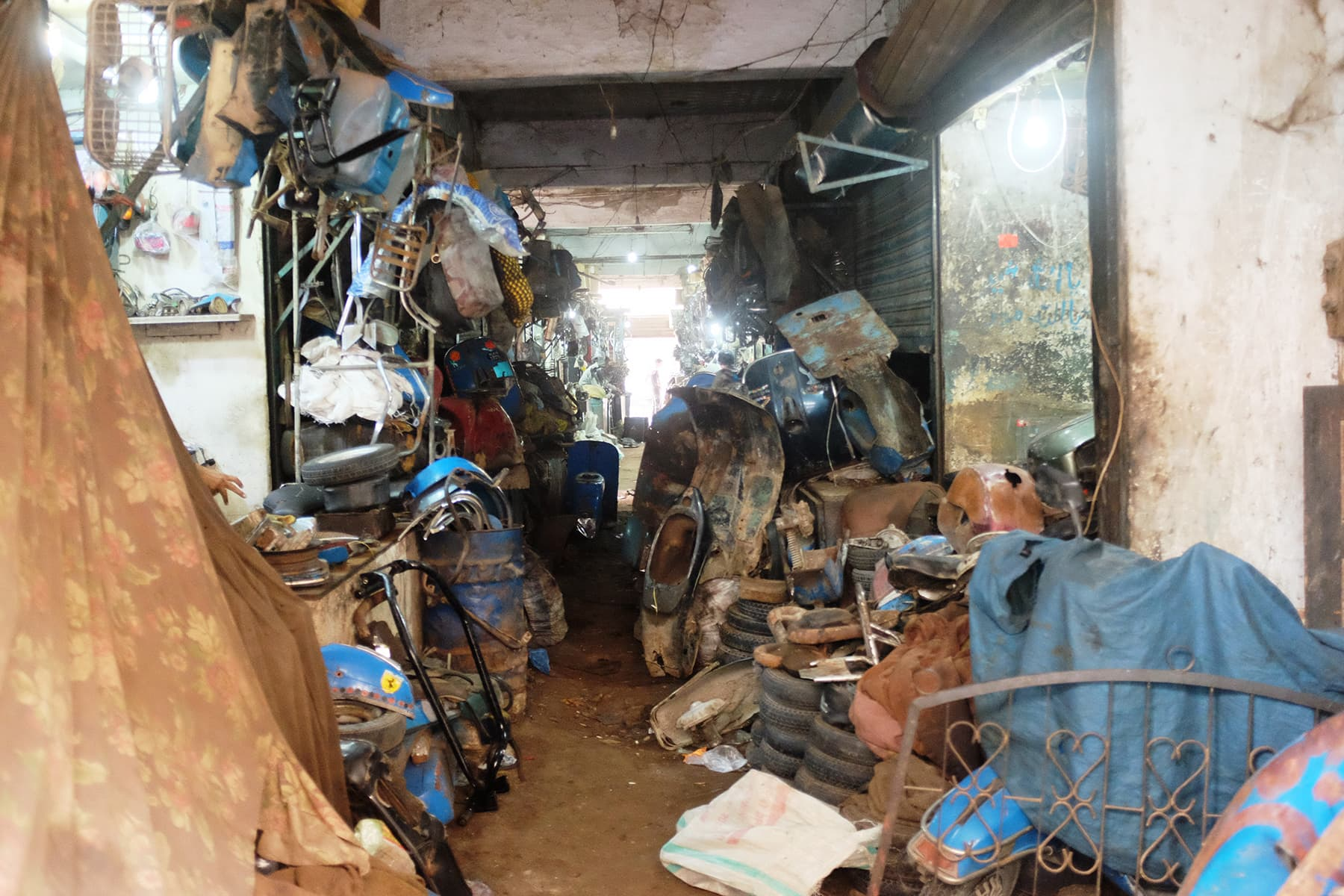 The narrow lane looks like a graveyard of Vespas and its spare parts.