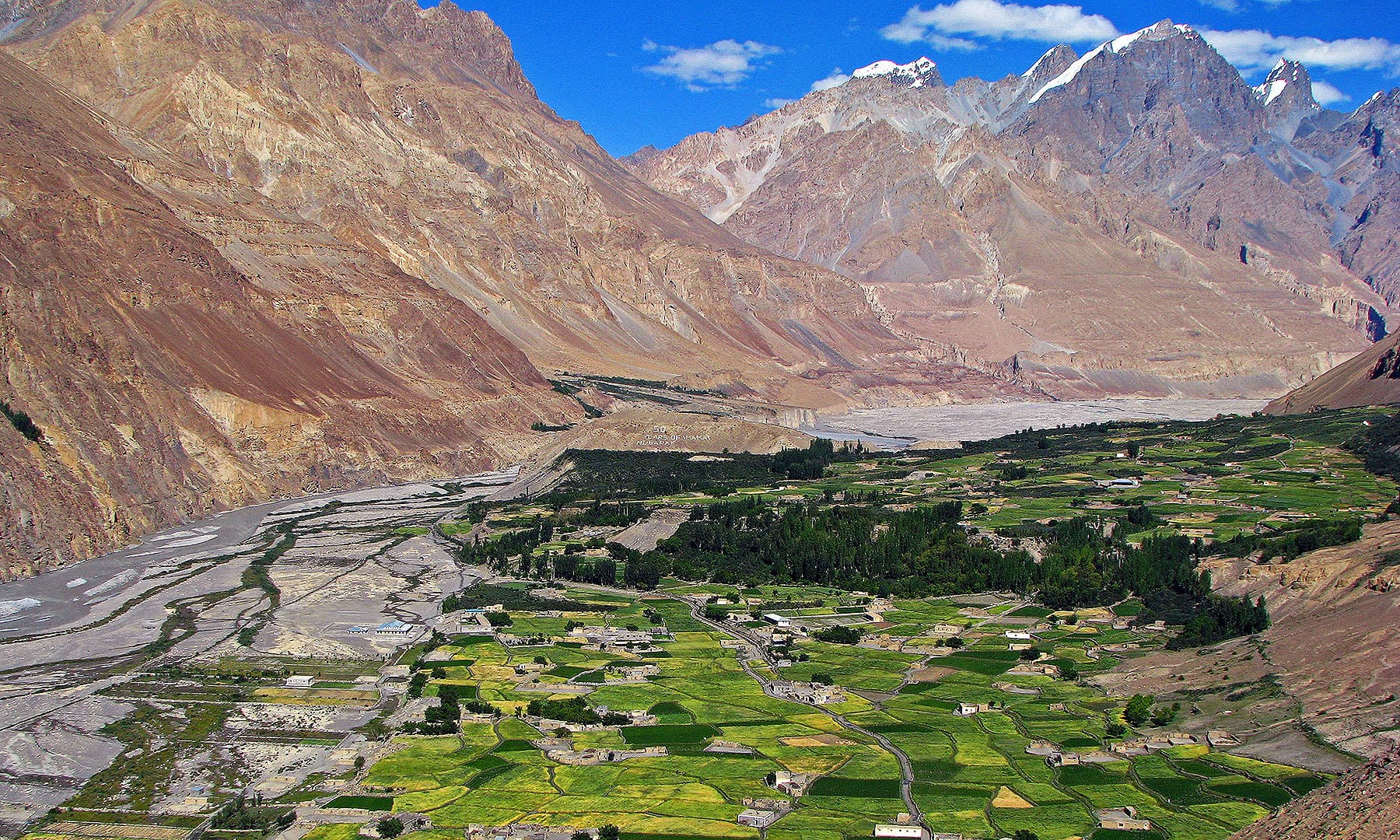 View of Central Shimshal and Khizerabad Village with the Sunrise Peak (Yeerghatak) in the backdrop. The small green patch across the Shimshal River is Band-e-Ser Village.