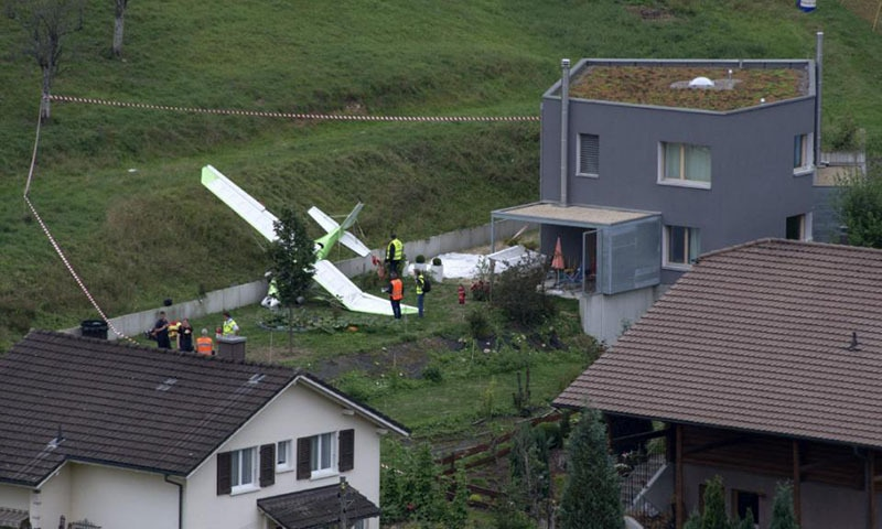 Firefighter stand beside a crashed plane crash, Sunday, 23 August 2015, in Dittingen, Switzerland. Two small planes crashed into each other just at an airshow in Dittingen, Switzerland, killing at least one person. —AP
