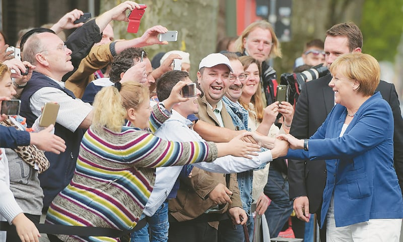 """Duisburg: German Chancellor Agela Merkel greets people on Tuesday after she arrived here for a """"citizen dialogue"""".—AFP"""