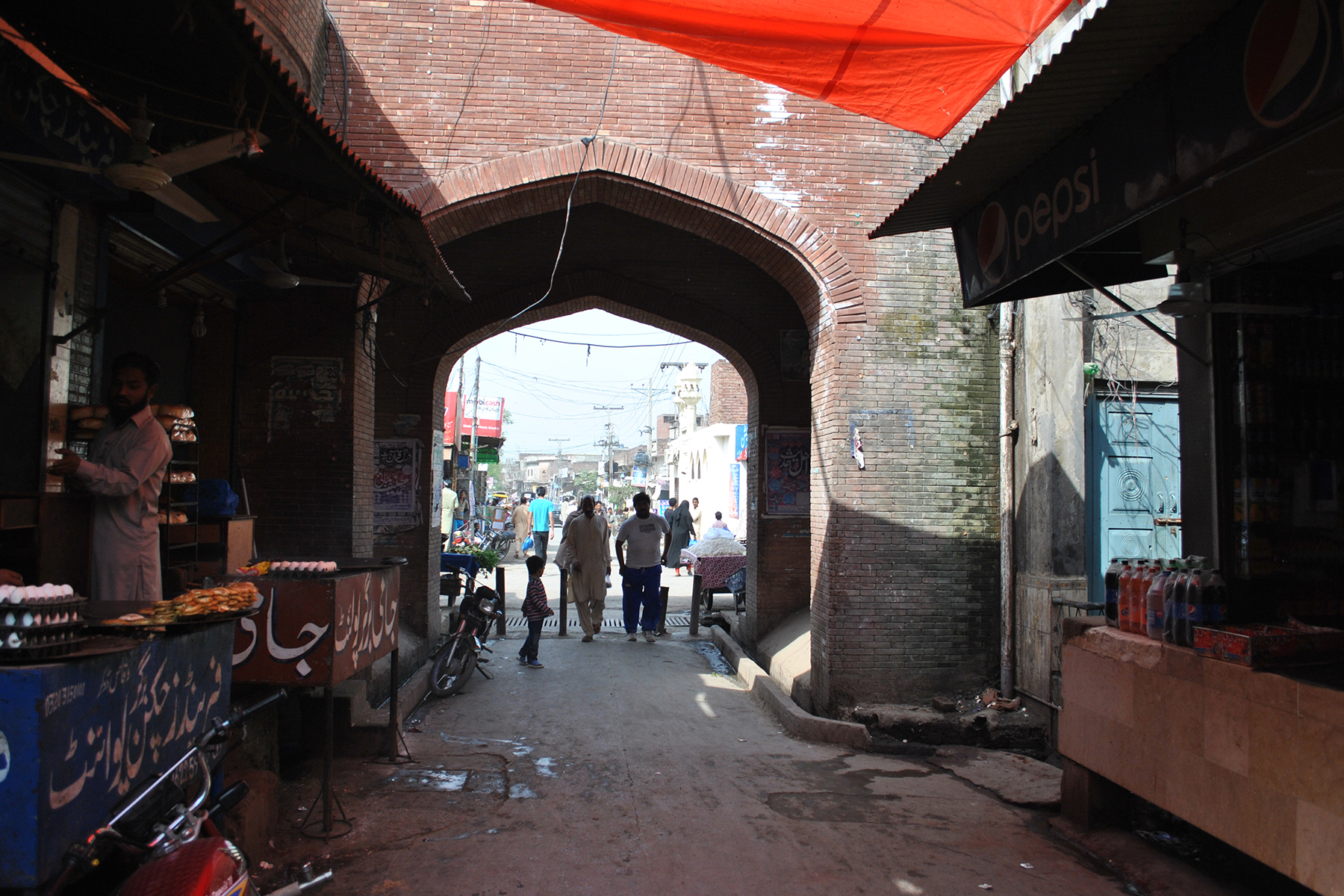The gate leads into a narrow crowded main market of Eminabad.