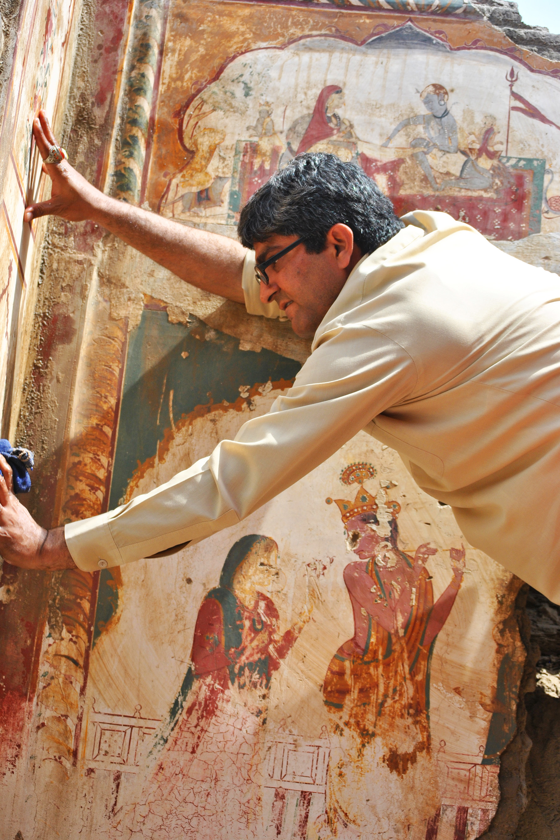 Passion for art: Dr Ghulam Abbas climbed up a ladder to wipe the dust off the fresco paintings on a facade of Diwan's haveli.