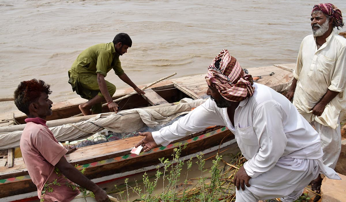 Fishermen prepare their boat for a trip down the river. -Photo by author