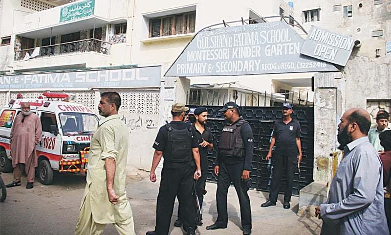Police personnel standing guard outside the school where two teenagers were found shot dead early on Tuesday. —Online