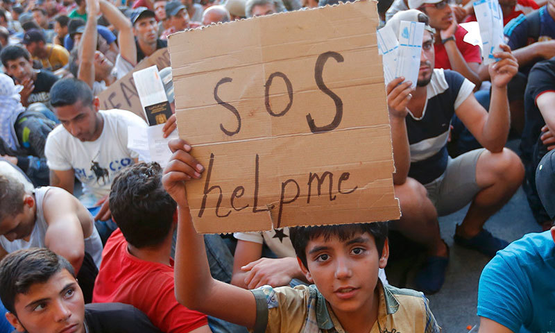 "A child holds a self-made placard reading ""SOS help me"" outside the railway station in Budapest, Hungary, Sept 2, 2015. - Reuters"