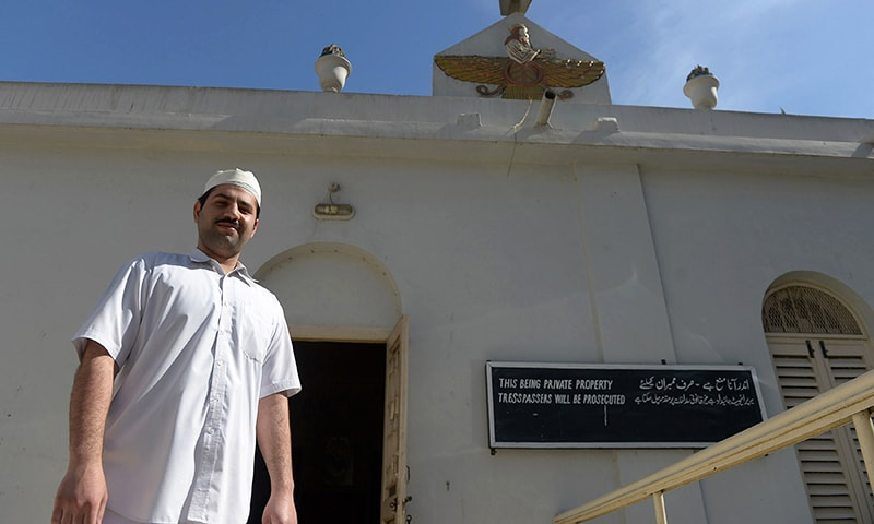 Pakistani Parsi priest walking past a temple in Karachi. — AFP