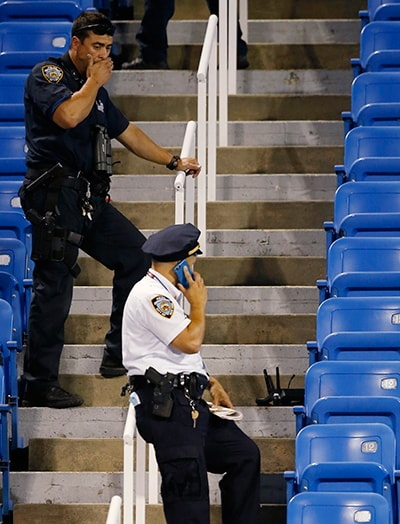 Police officers investigate the sight after a drone crashed in the corner of Louis Armstrong Stadium during a match. — AP