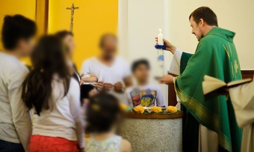 Pastor Gottfried Martens lights a candle during a service to baptize people from Iran, in the Trinity Church in Berlin. ─AP