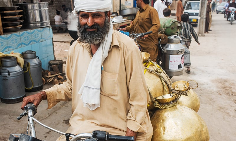 Sanaullah the milk seller delivers milk on his motorcycle