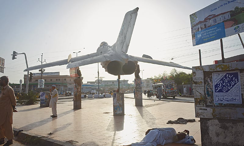 People find shade under an old PAF aircraft.—White Star