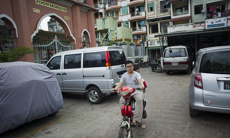 Muslim boys riding a bike near the Joon Mosque in Myanmar's second biggest city of Mandalay. ─ AFP/File