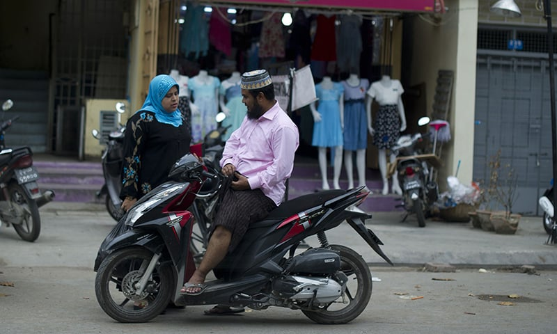 Muslims chatting along a street in Mandalay. ─ AFP/File