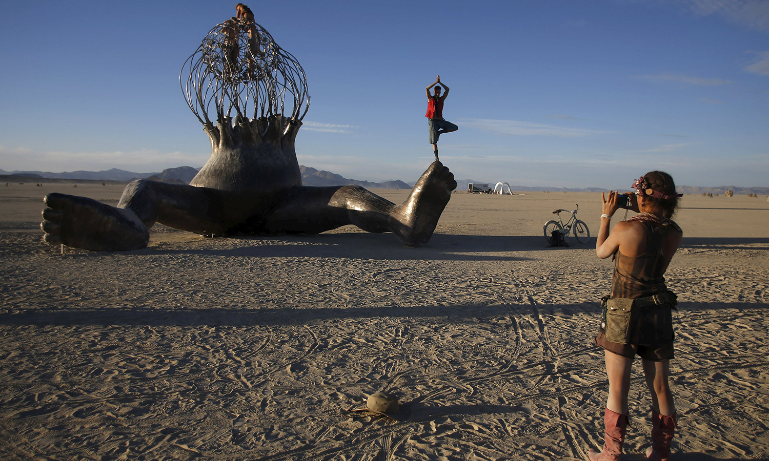 """Kenyon Acton (R) takes a photo of Ian Bennett posing on an art installation during the Burning Man 2015 """"Carnival of Mirrors"""" arts and music festival in the Black Rock Desert of Nevada, September 6, 2015. — Reuters"""