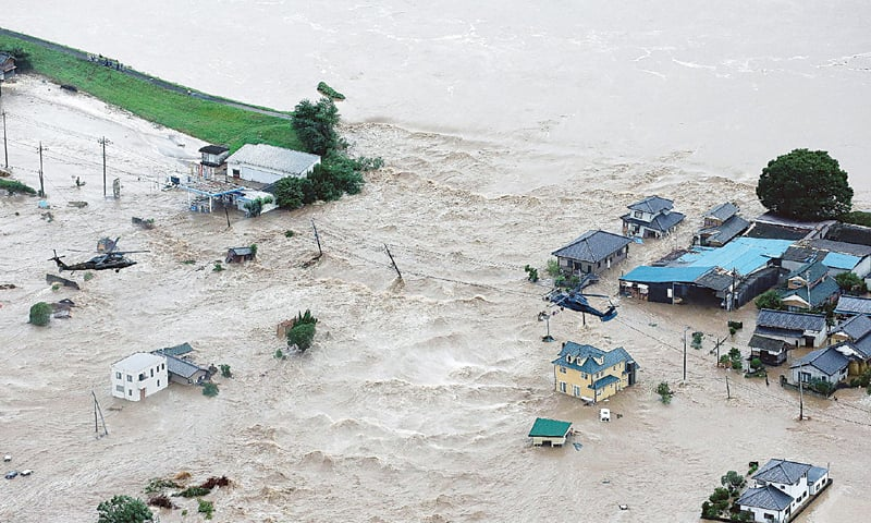 Joso (japan): Floodwaters flow from the overflowing Kinugawa river enter a residential area here on Thursday.—AFP