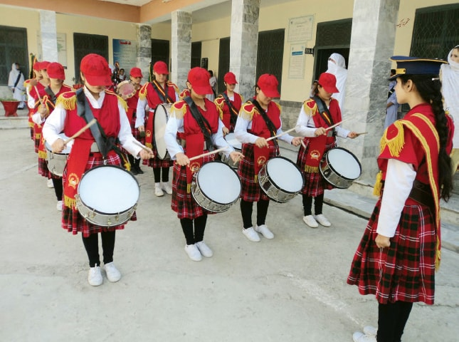 Young drummers welcome the newly enrolled students at a girls school in Mingora on Thursday. (Below) MPA Nadia Sher Khan enrolling a girl. — Dawn