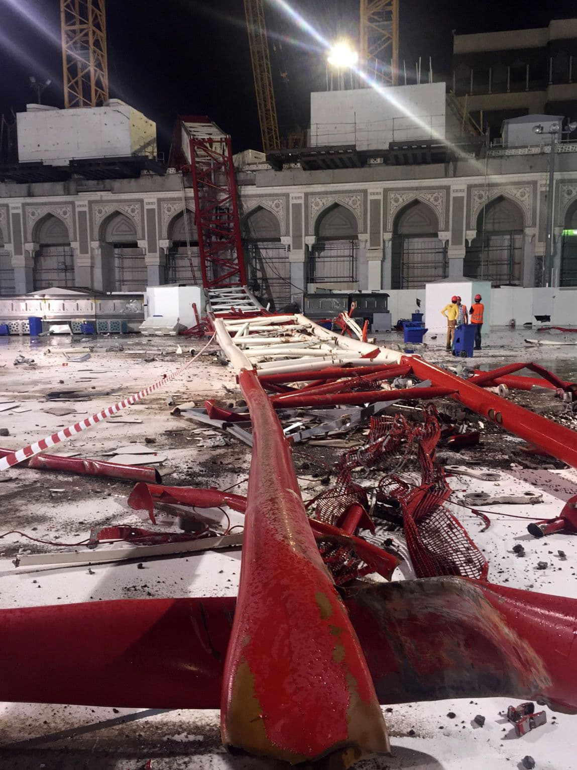Saudi emergency teams stand next to a construction crane after it crashed into the Grand Mosque. —AFP