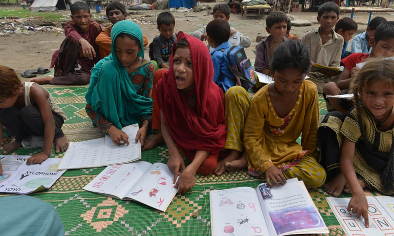 Children at a slum in Lahore attend class at a makeshift, open air school.—White Star
