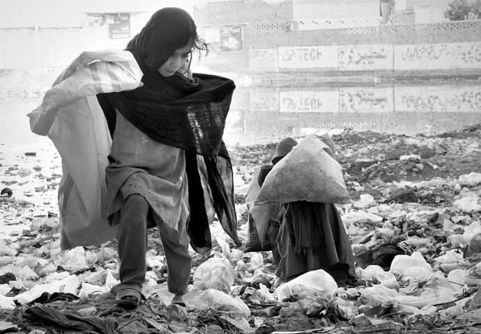 Scavenger girls rummage through garbage in Peshawar. The young ones collect recyclable material which their families sell and earn a living.—White Star