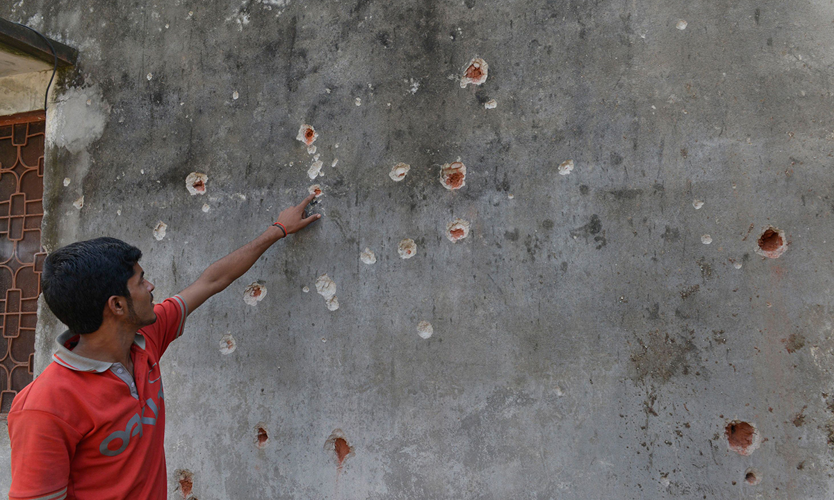 A resident points to bullet holes in the wall of his home, allegedly caused by shells fired by Indian troops. —AFP/File