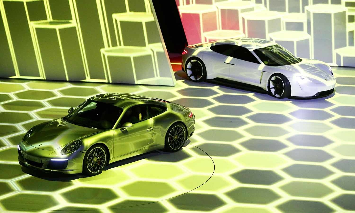 The new Porsche 911 Carrera S (L) and concept car Mission E are presented during the Volkswagen group night ahead of the Frankfurt Motor Show (IAA). ─ Reuters