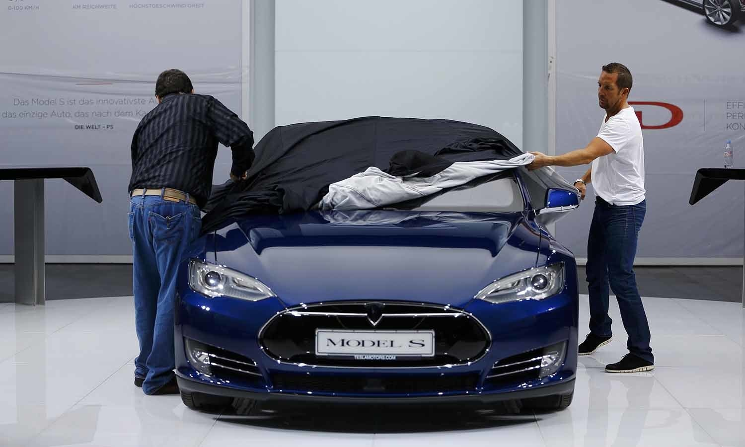 Employees cover a Tesla Model S car during the media day. ─ Reuters