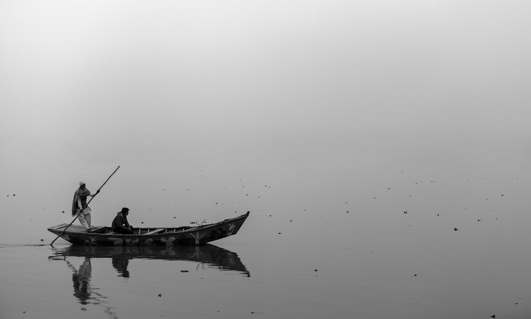 دھند سے لپٹے چناب میں کشتی رانی.— فوٹو سید مہدی بخاری۔