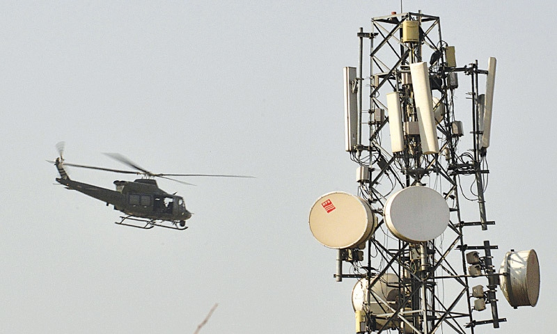 A helicopter patrols over a PAF area and soldiers take positions outside the camp.—AFP