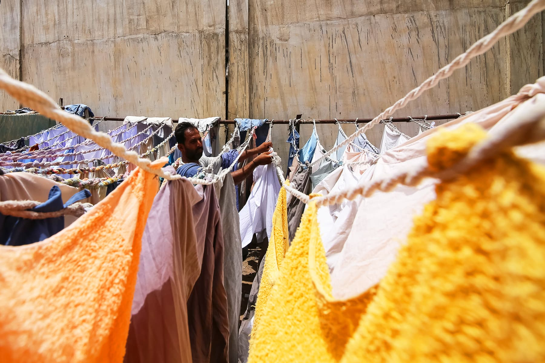A dhobi puts up laundered clothes for drying in the sun.