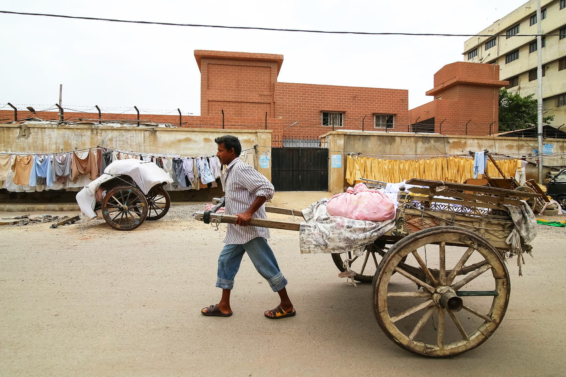 Raja, Faheem's brother pulls a cart with freshly laundered clothes.