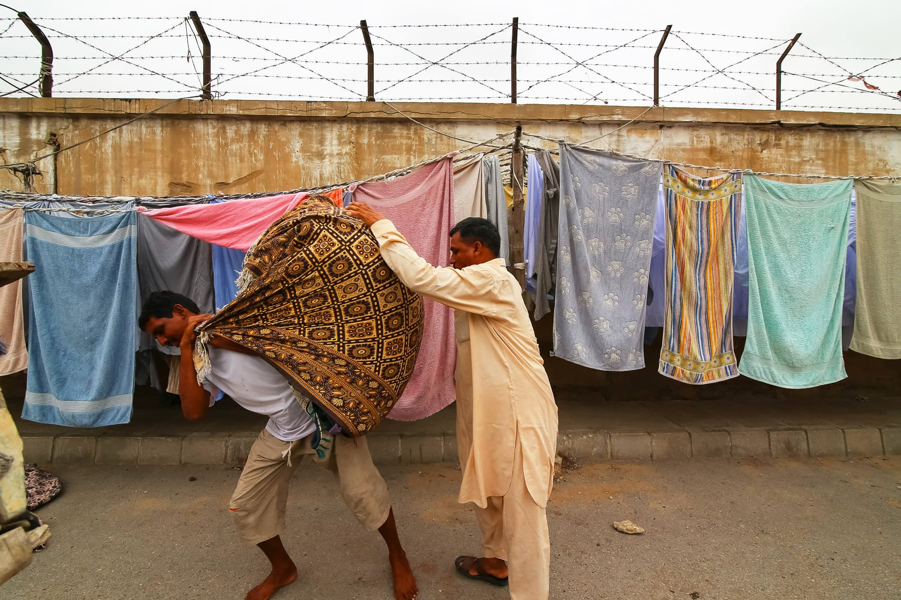 Waseem, Faheem's brother loads a pack of laundered and sunned clothes for delivery to customers.