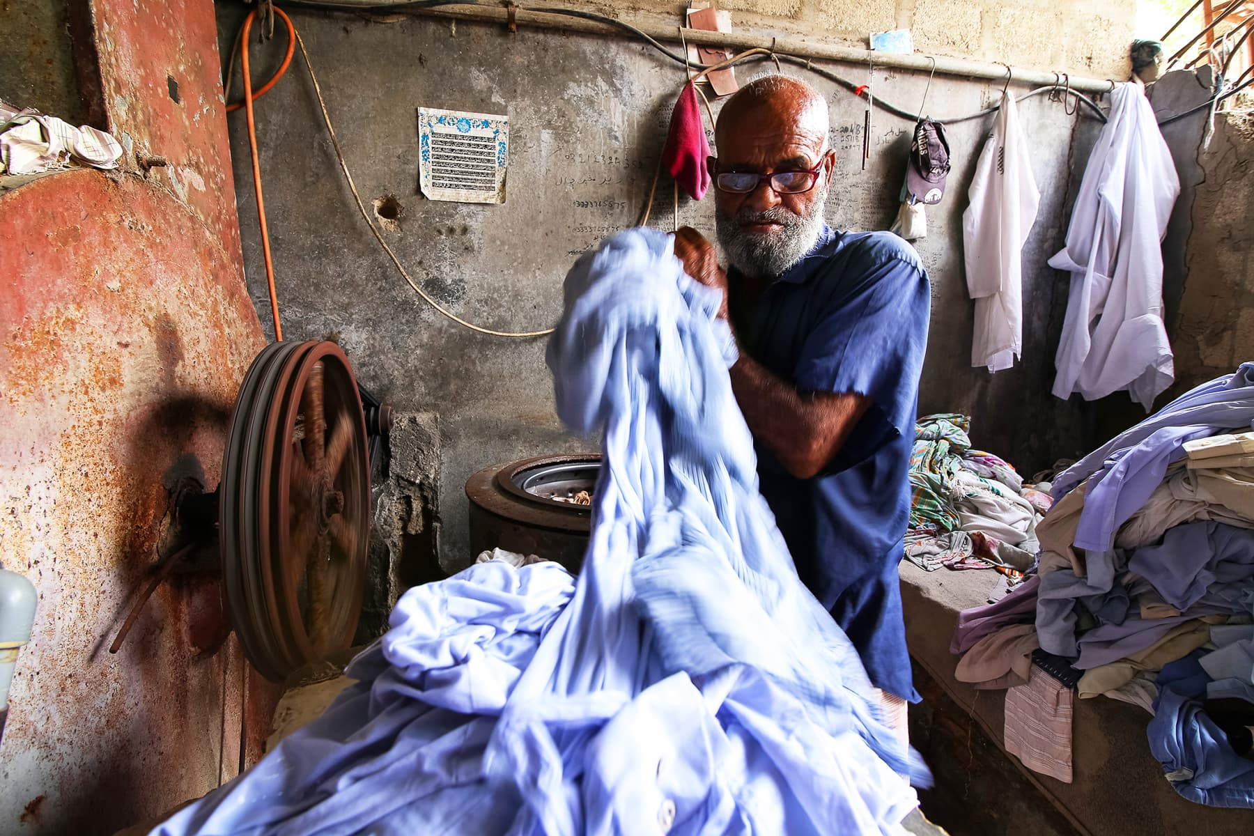 Hanif transfers washed and wet clothes to put into the dryer to spin out the water.