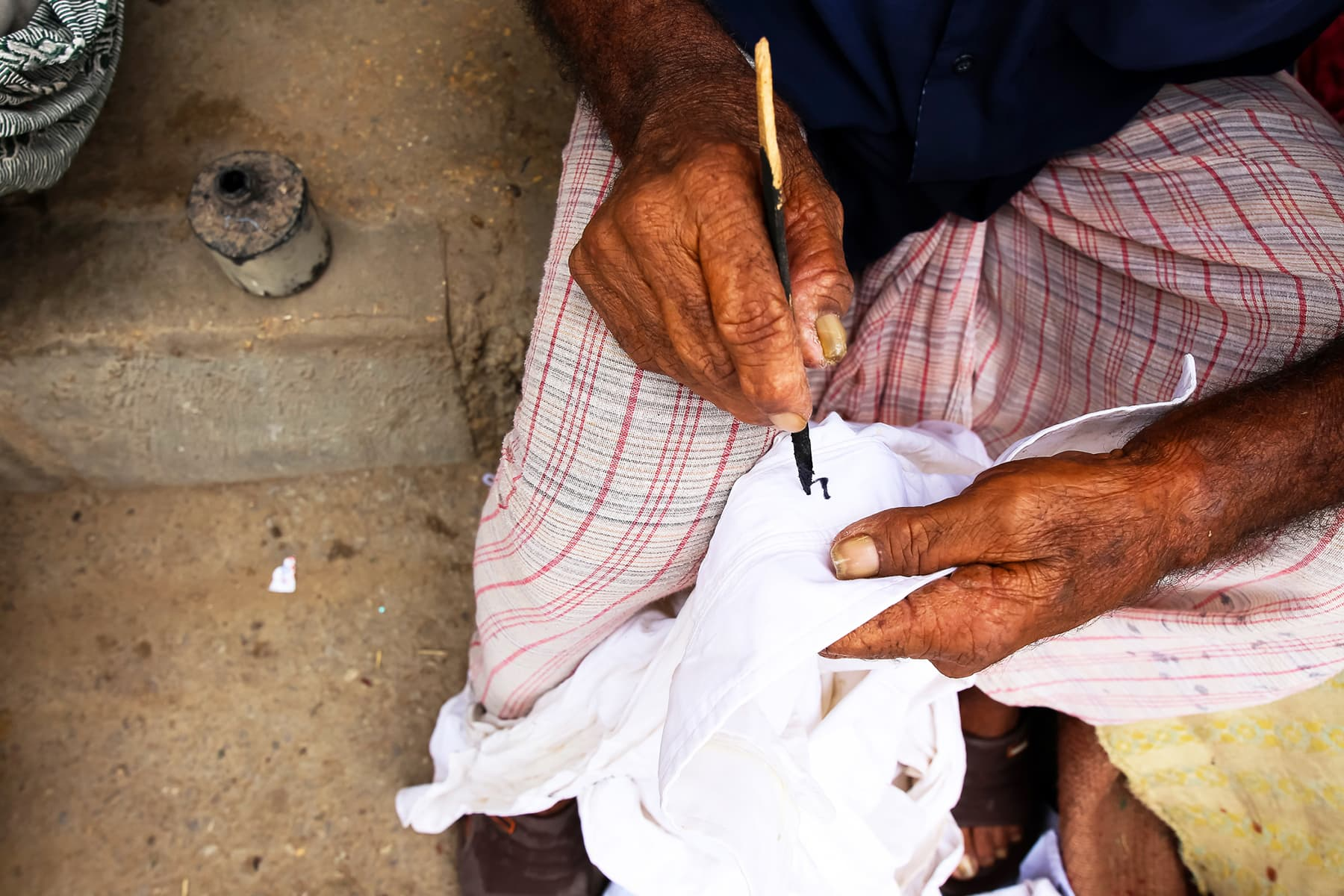Hanif marks each cloth to categorise them according to the batch number and owner.