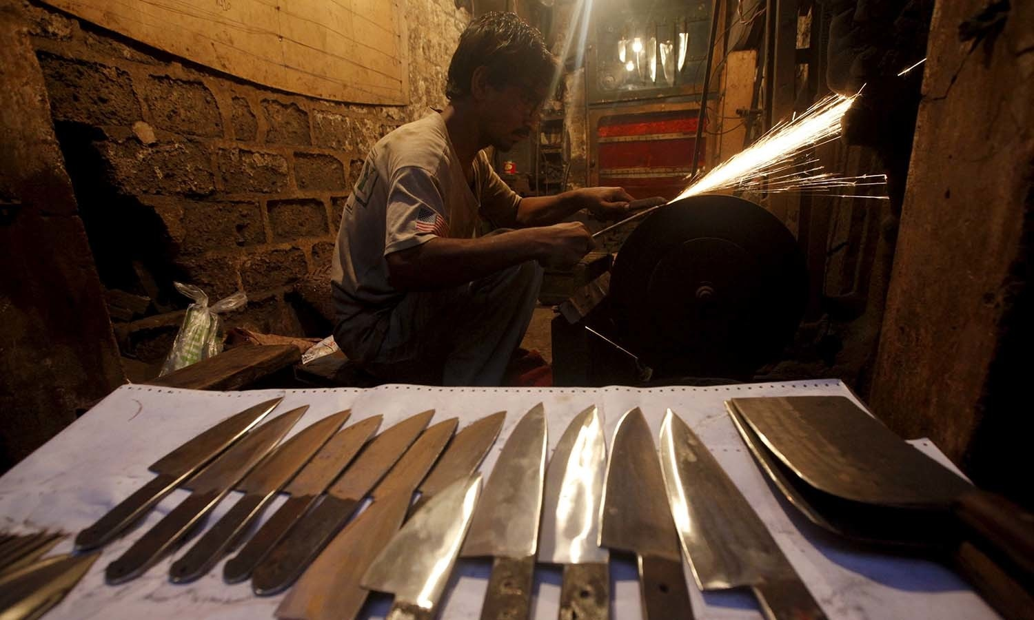 A man sharpens knives to be sold ahead of the Eidul Azha festival in Karachi. ─ Reuters