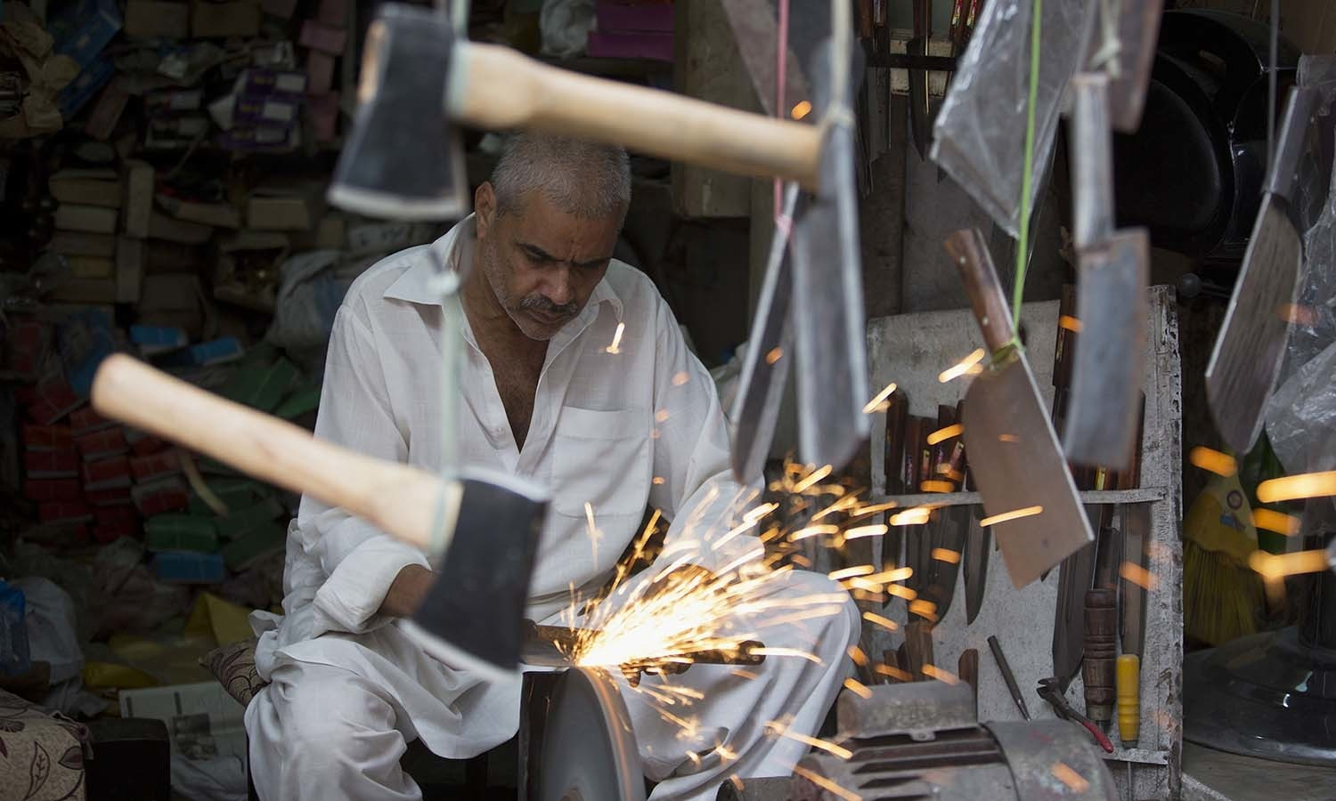A vendor sharpens a knife for the upcoming Muslim festival of Eidul Azha in Rawalpindi. — AP