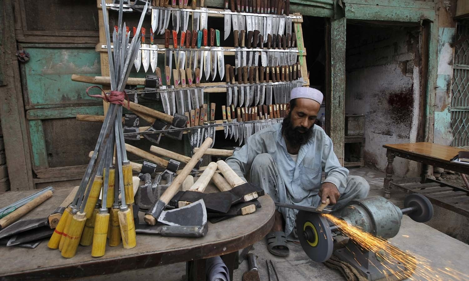 A vendor sharpens a knife for the upcoming Muslim festival of Eidul Azha in Peshawar. — AP