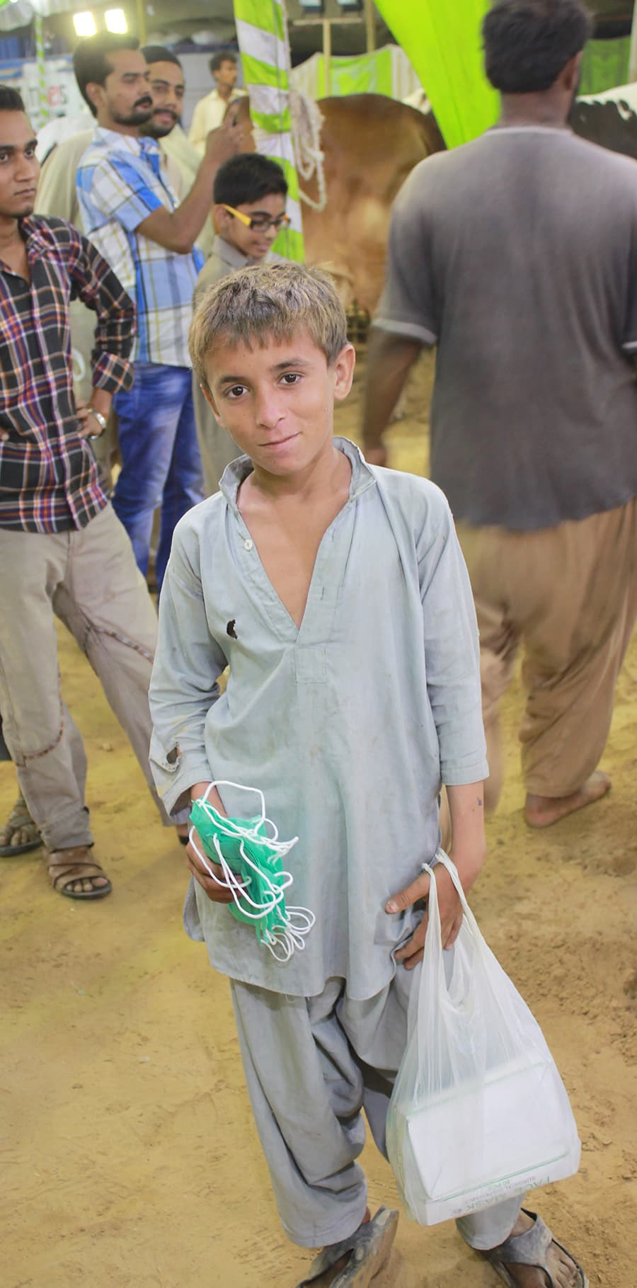 A young boy who sells masks to visitors at the cattle market poses for a photo. —Adeel Ahmed