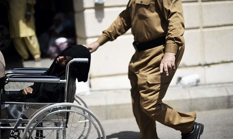 A Saudi policeman pushes a wheelchair with an injured pilgrim outside an emergency hospital following a deadly stampede in Mina. - AFP