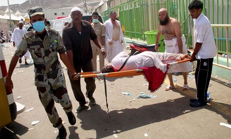Haj pilgrims and Saudi emergency personnel carry a woman on a stretcher at the site where at least 450 were killed and hundreds wounded in a stampede in Mina. - AFP