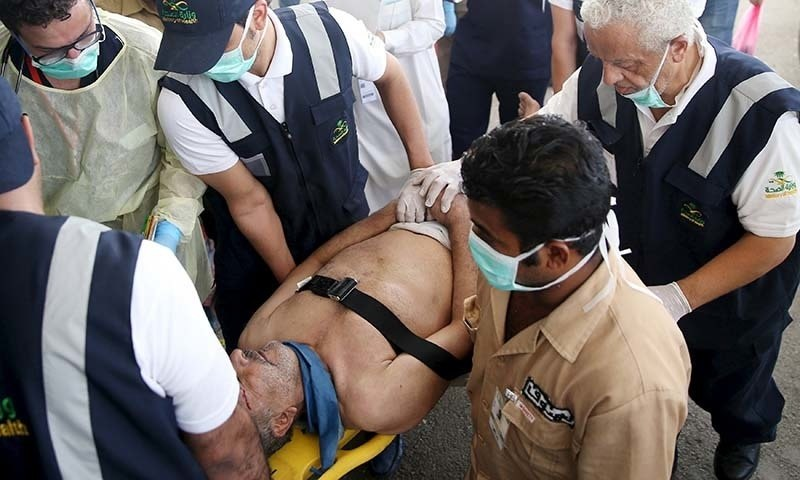 Medical staff carry a way wounded pilgrim following a crush caused by large numbers of people pushing at Mina. - Reuters