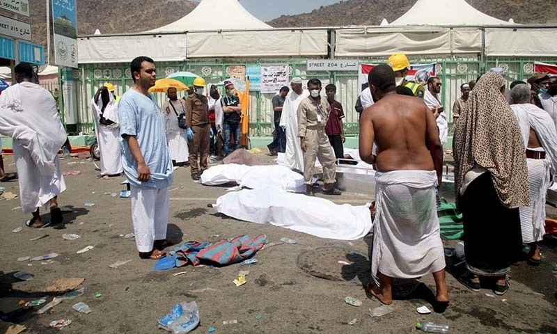 Haj pilgrims and Saudi emergency personnel stand near bodies at the site where at least 450 were killed and hundreds wounded in a stampede in Mina. - AFP
