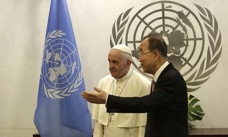 Pope Francis, left, talks with United Nations Secretary Ban Ki-moon at the United Nations headquarters. — AP