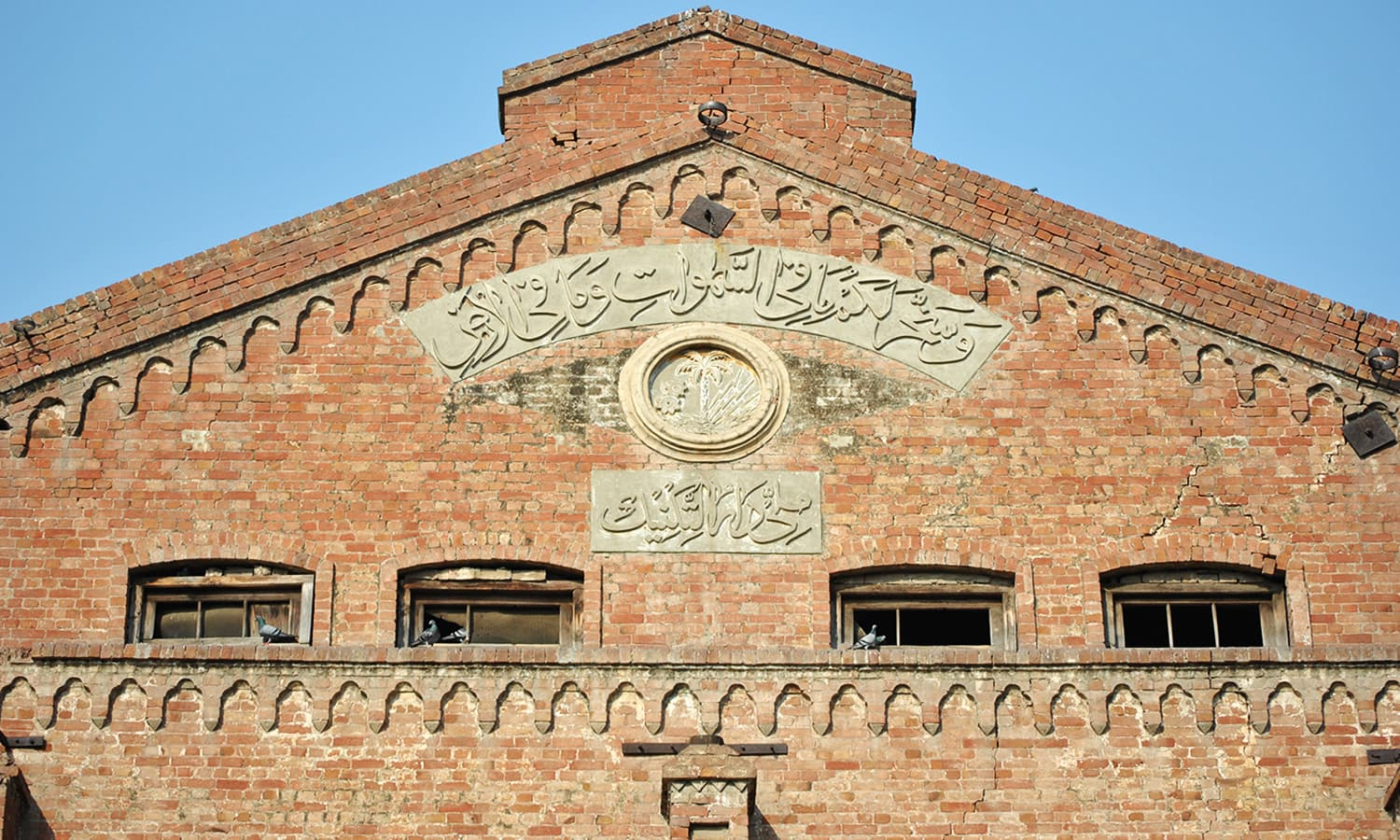 The upper plaque is inscribed with a Quranic verse. The lower one reads 'National Technical Institute' (The hall was used for technical education after the partition).
